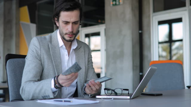 Businessman counting money in office