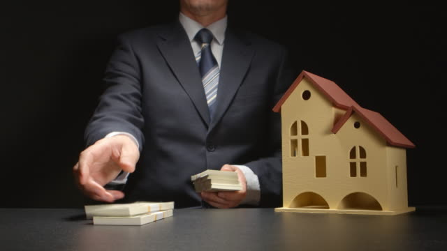 vídeos y material grabado en eventos de stock de hombre de negocios cuenta con un dinero y cerca de un casa modelo en una tabla - hipotecas y préstamos