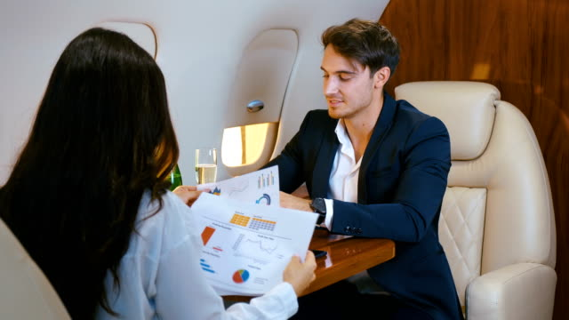 vídeos de stock e filmes b-roll de businessman counts money, celebrating success, with champagne, flying in a private plane. concept of a successful business deal. business people celebrate financial success - elegante