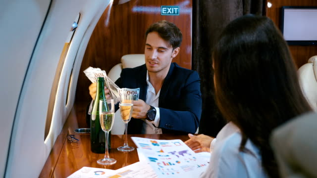 Businessman counts money, dollar bills, celebrating success, with champagne, flying in a private plane. Concept of a successful business deal.
