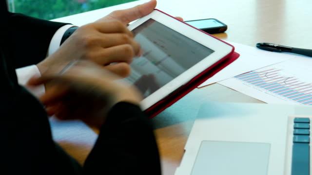 businessman demostrates his work on digital tablet in meeting room - zagadnienia filmów i materiałów b-roll