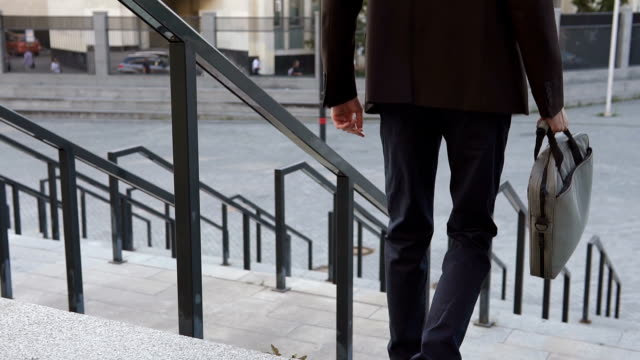 Businessman descends the stairs in a big city video