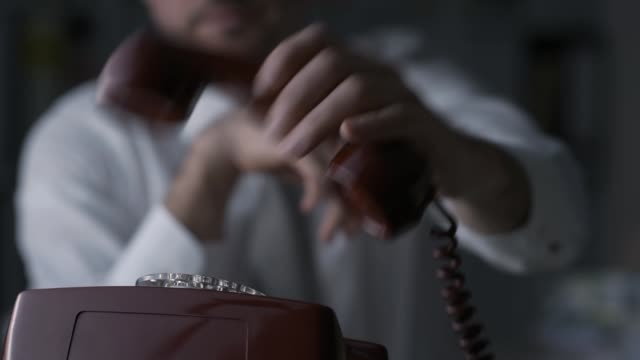 Businessman dialing a number on a vintage phone Businessman dialing a number on a vintage rotary dial phone in the office, hand close up telephone receiver stock videos & royalty-free footage