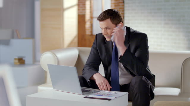 Businessman dialing number, making business phone call in office video