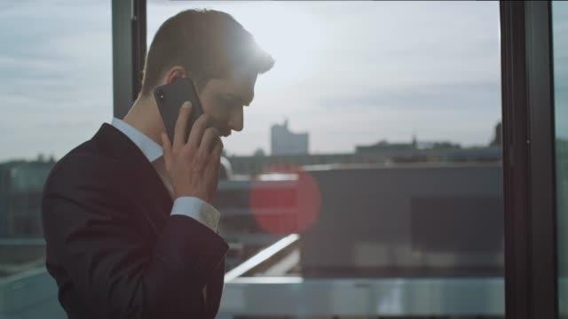 affärs man diskuterar på mobil telefon nära fönster - kostym sida bildbanksvideor och videomaterial från bakom kulisserna