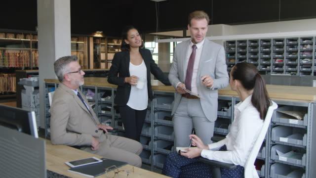uomo d'affari che discute con i colleghi in carica - 20 o più secondi video stock e b–roll