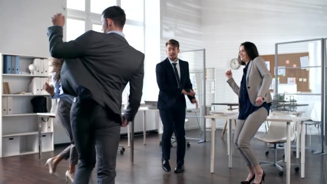 businessman doing handstand while dancing with colleagues in office - acrobazia video stock e b–roll