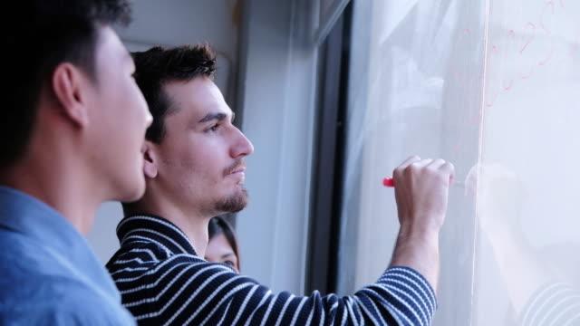 vídeos de stock, filmes e b-roll de empresário de sucesso de desenho no vidro mostrando estudante em palestra universidade criativas ideias de ensino, compartilhando dados em vidro moderno laboratório - explicar