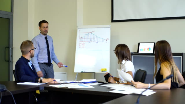 businessman draws a graph on the whiteboard to his colleagues video