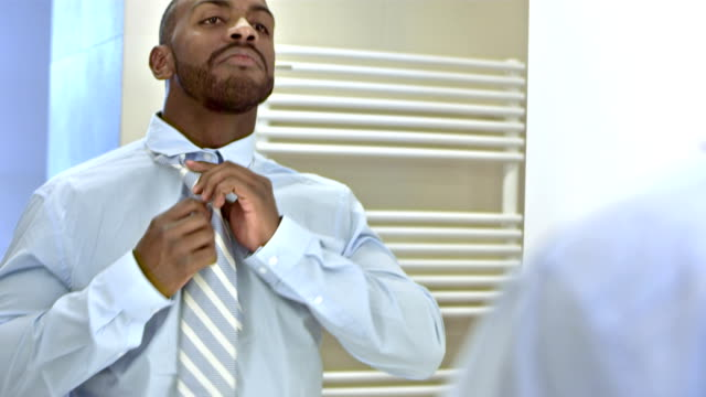 MS Businessman Dressing For Work HD1080p: Medium shot of a mid-adult businessman dressing for work in front of a mirror in the bathroom. body care stock videos & royalty-free footage