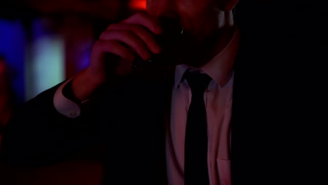 Businessman drinking alone in bar, pondering over business solutions, closeup video