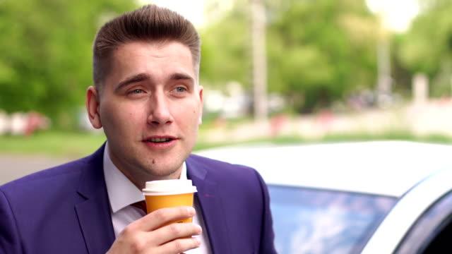 Businessman drinking coffee near the car on street video
