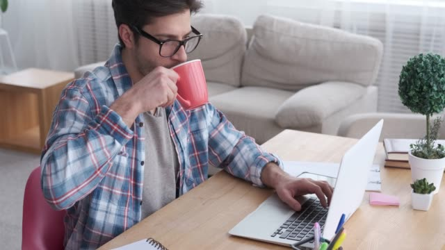 Businessman drinking coffee while working on laptop video