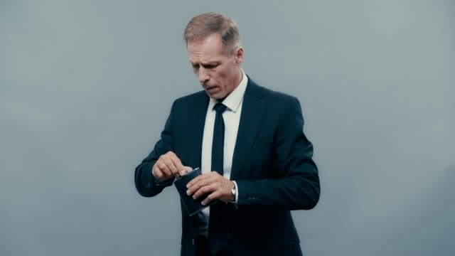 businessman drinking from flask and showing shh