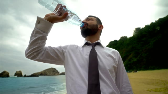 Businessman Drinking Water on the Beach - 4K Resolution video