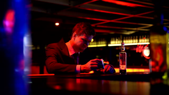 Businessman drinking whiskey in bar, rubbing head in desperate, bankruptcy video