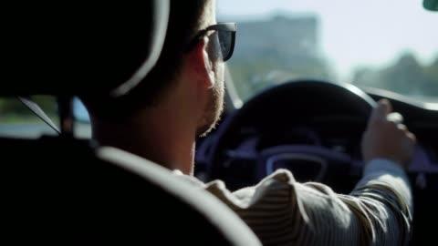 vídeos y material grabado en eventos de stock de conducir un coche en la ciudad durante el día del empresario - conducir