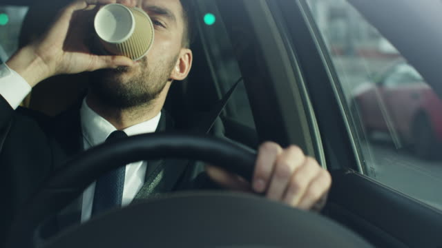 businessman driving a car in the morning, drinking coffee. - cup stock videos & royalty-free footage