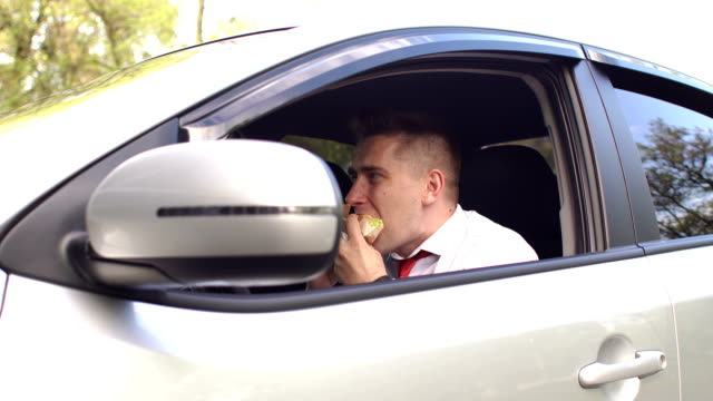 Businessman eating a Burger sitting in the car. video