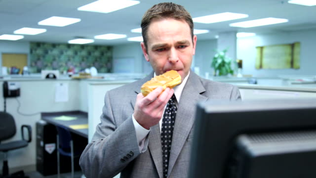 Businessman eating a doughnut and making mess video