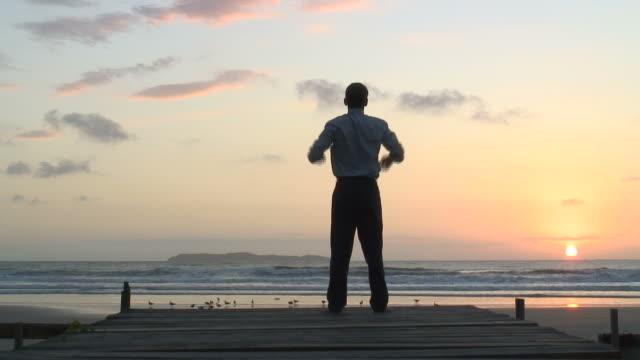 ビジネスマンのお客様は、ビーチの朝日 ビデオ