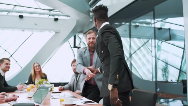 Businessman entering an office and shaking hands