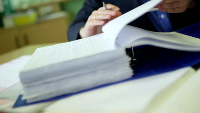 Businessman examining documents at desk video