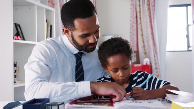 businessman father sitting at desk in sons bedroom helping him with homework - praca domowa filmów i materiałów b-roll