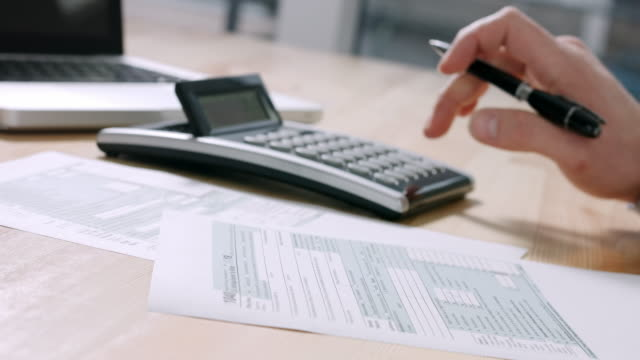 Businessman filling 1040 tax form Closeup of US tax form 1040 and businessman hand calculating and filling report paper at the office. 4k footage resolution. taxes stock videos & royalty-free footage