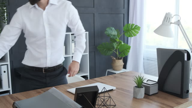 Businessman finishing work and packing belongings in box