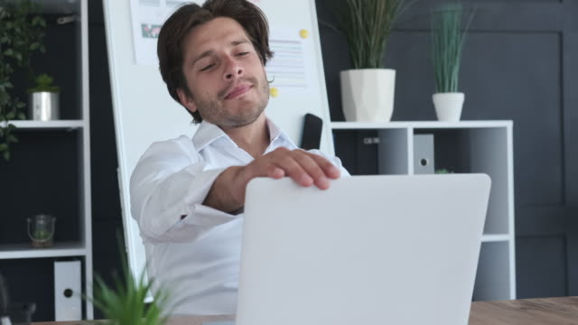 Businessman finishing work on laptop and relaxing on chair video