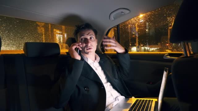 vídeos y material grabado en eventos de stock de empresario frustrado y enojado hablando por teléfono móvil. - equipo informático