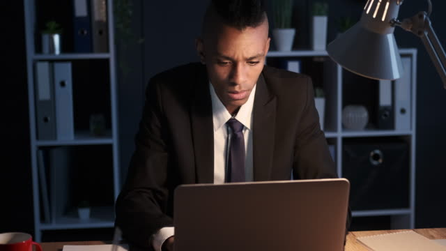 Businessman frustrated by bad news on laptop late in night office