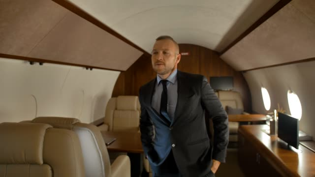 Businessman funny dancing inside of private jet