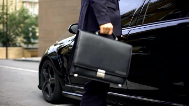 uomo d'affari salire in auto di lusso, guidare a un incontro importante, millennial - entrare video stock e b–roll