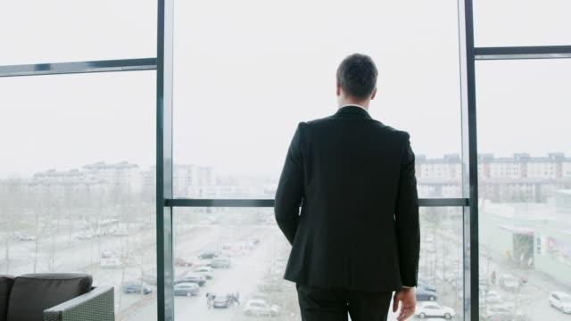 affärsman som reser sig upp från skrivbord i office, realtid - kameraåkning på räls bildbanksvideor och videomaterial från bakom kulisserna
