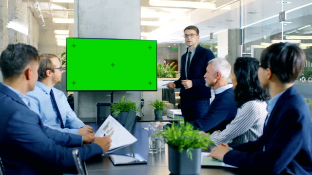 businessman gives report/ presentation to his business colleagues, pointing at green chroma key screen wall tv. - sales stock videos & royalty-free footage