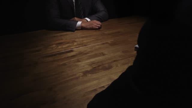 vídeos de stock e filmes b-roll de businessman giving money to his partner on the table in the dark - corruption