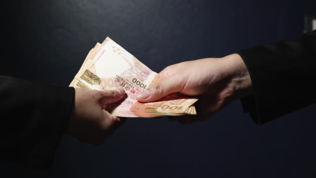 Businessman giving money to his partner.