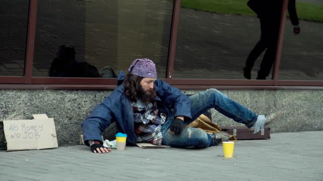 ホームレスにお金を与える実業家 - 不吉点の映像素材/bロール