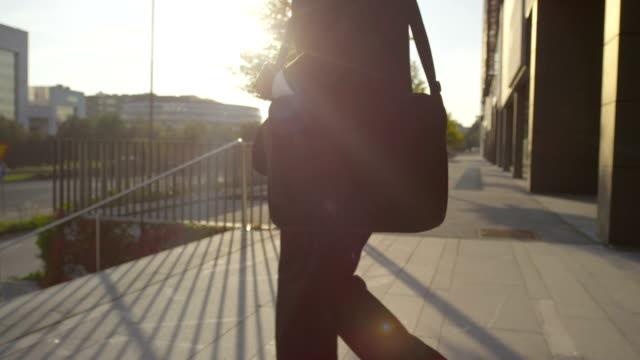 close up: businessman going home from the office building - walking home sunset street bildbanksvideor och videomaterial från bakom kulisserna