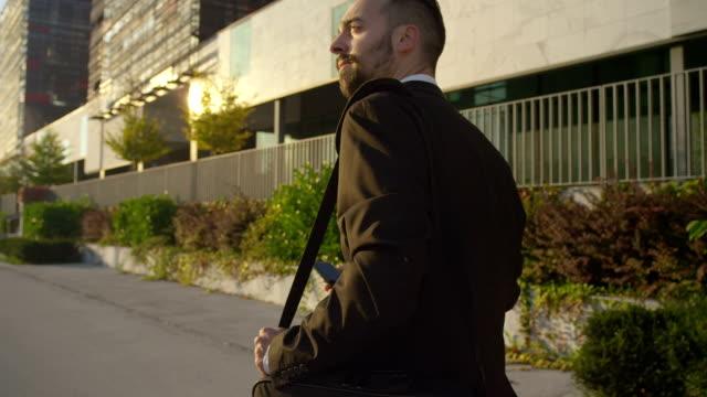 close up: businessman going to work to the business district - walking home sunset street bildbanksvideor och videomaterial från bakom kulisserna