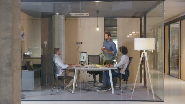vídeos de stock e filmes b-roll de businessman greeting colleagues at creative office - secretária mobília