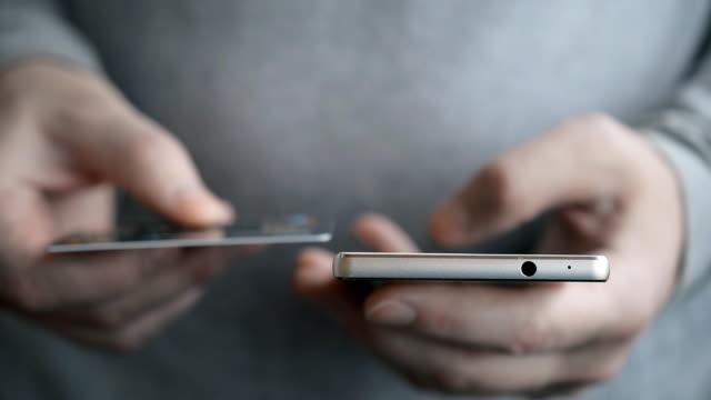 ビジネスマンは、クレジットカードやスマートフォンでオンライン決済を行う灰色のシャツでクローズアップを手渡します, オンラインショッピング, ライフスタイル技術の概念 - グリーティングカード点の映像素材/bロール