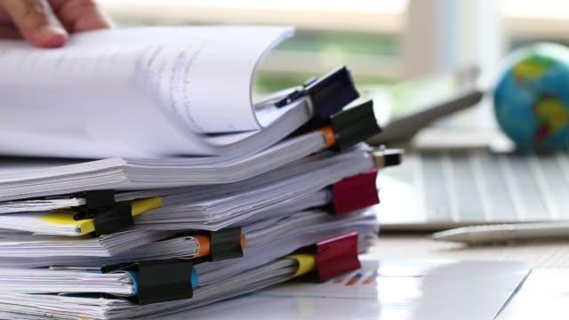 affärsman händer som håller pennan för att arbeta i högar av pappersfiler söka information affärsrapport papper och högar av oavslutade handlingar åstadkommer på laptop dator skrivbord i moderna kontor - lagbok bildbanksvideor och videomaterial från bakom kulisserna