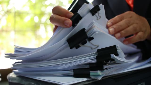 Businessman hands searching unfinished documents stacks of paper files on office desk for report papers, piles of papers sheet achieves with clips on desks, Document is written, drawn,presented Businessman hands searching unfinished documents stacks of paper files on office desk for report papers, piles of papers sheet achieves with clips on desks, Document is written, drawn,presented law stock videos & royalty-free footage