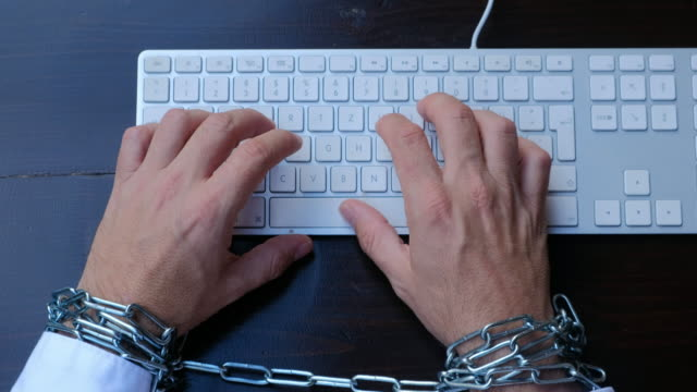 Businessman hands tied with chains on wrists typing on laptop keyboard video