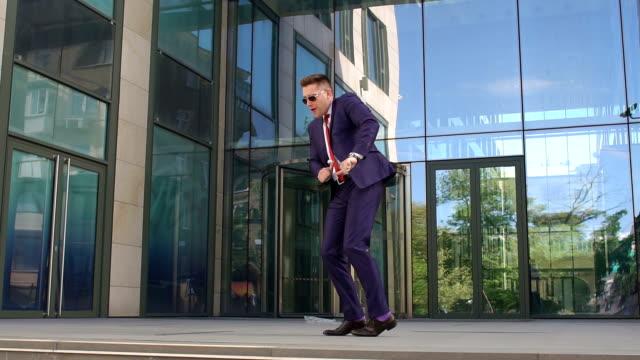 事務所ビルのそばで踊って幸せな実業家。 ビデオ