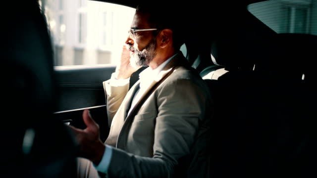 Businessman having a phone call in a car Mid aged businessman sitting in a back seat of a parked luxury sedan talking on a cell phone and hearing some good news. He has very neatly groomed beard and wearing eyeglasses. He's gesturing and looking through window. Shot through window on the opposite side. 4k video. wealth stock videos & royalty-free footage