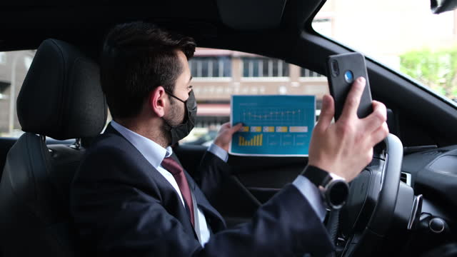 Businessman having video call while traveling in car